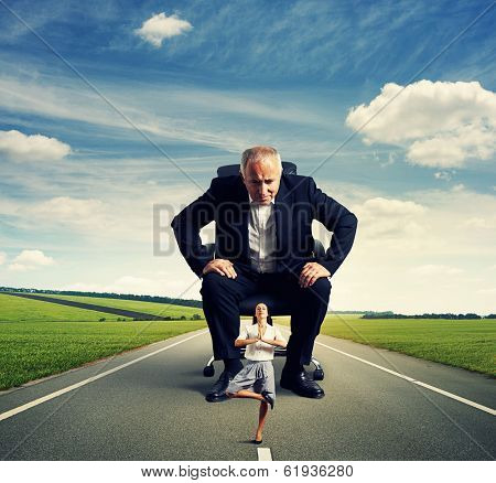 senior man sitting on the office chair and scrutinizing meditation smiley woman at outdoor