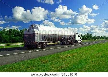 Speeding truck delivering gasoline on highway blurred because of motion