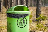 Green trash basket with sign pictogram in forest, plastic bag inside visible. poster