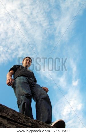 Low Angle Side View Of Young Man Stays On The Stone Edge