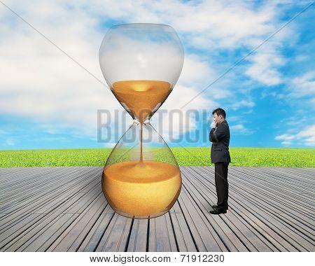 Standing Businessman Watching The Hourglass
