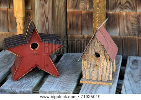 Two Americana style birdhouses set together on old, weathered wood bench. poster