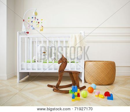 Empty nursery room with basket toys and wooden horse poster