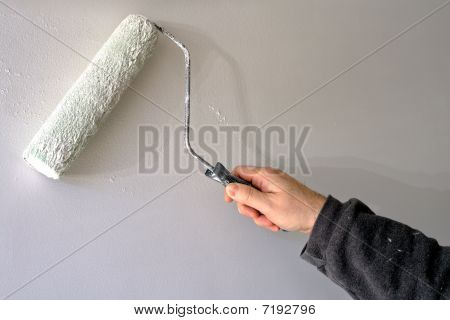Painter Painting A Wall With A Roller And White Paint