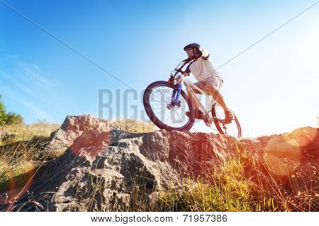 Mountain biker in action across rocks against blue sky concept for healthy lifestyle, exercise and extreme sports