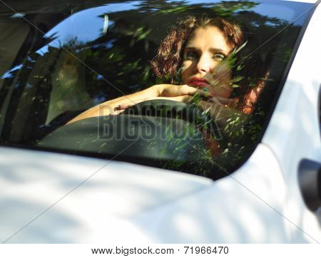 Woman In  White Car Looking Bored