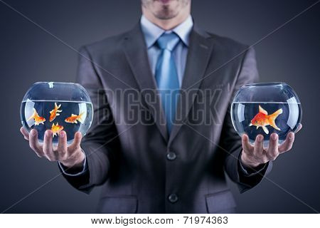 Businessman holding in both hands  fishbowl with goldfishes