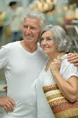 Portrait of beautiful elderly couple in shopping mall poster