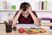 Young student is desperate while doing homework at school poster