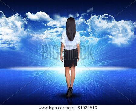 Businesswoman walking against blue landscape with rising sun