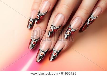 Red and black art design on nails.