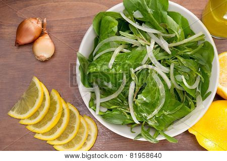 Rocket / Roquette / Arugula / Rucola salad leaves npresented with ingredients on a wooden plate