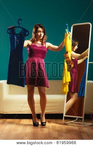 Fashion and shopping. Woman preparing to party trying dress choosing clothing. Attractive young woman shopper looking in mirror standing in clothes store. poster