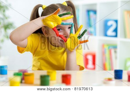 cute kid have fun painting her hands