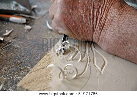 Hands Of The Craftsman Carve A Bas-relief In Wood
