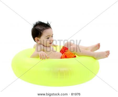 Adorable Boy In Swimsuit Sitting In Green Inner Tube Over White