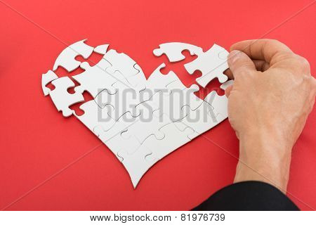 Person Solving Heartshape Jigsaw Puzzle