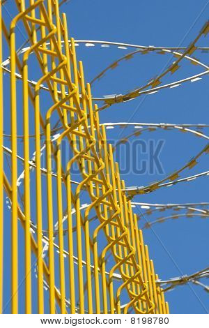 bright yellow fence with barbed wire on a background of blue sky poster