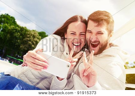 outdoors photo of joyous couple showing peace sign and taking selfie by mobilephone