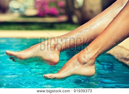 Tanned feet with pedicure compared to the pool and exotic nature