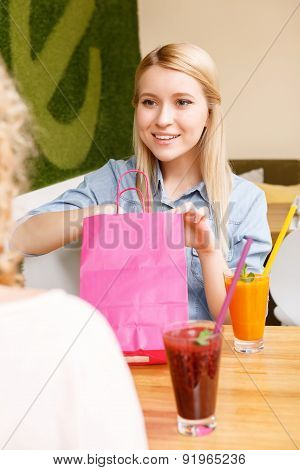 Young woman poking in paper bag