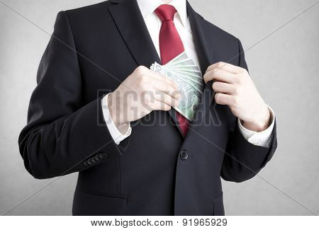 Corruption. Man putting polish money in suit jacket pocket.