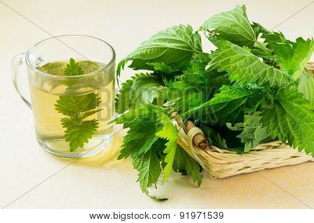 Nettle Leaves In A Basket And An Infusion In A Mug