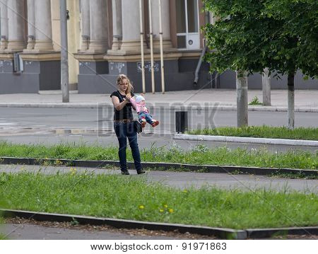 Makeevka, Ukraine - May 29, 2015: Young Mother Playing With Her Daughter On The Main Street Of The