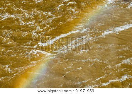 Vivid Rainbow Across Churning Muddy River.