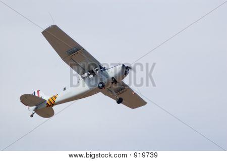 a cessna bird dog flies past at an air show. poster