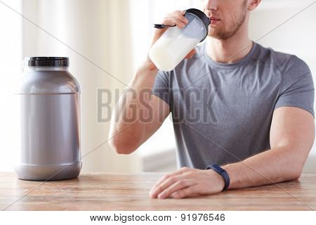 sport, fitness, healthy lifestyle and people concept - close up of man in fitness bracelet with jar and bottle drinking protein shake