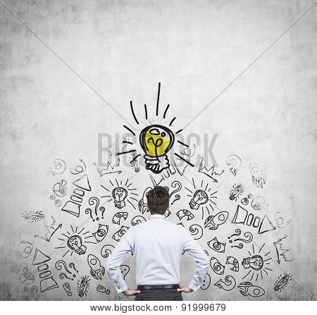 Rear View Of The Young Manager, Who Is Trying To Find New Idea. Business Icons And An Yellow Light B