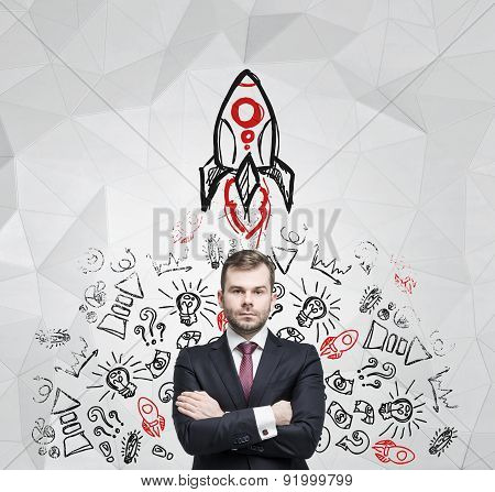 Young Manager With The Crossed Hands Is Thinking About New Business Ideas. Business Icons And A Rock