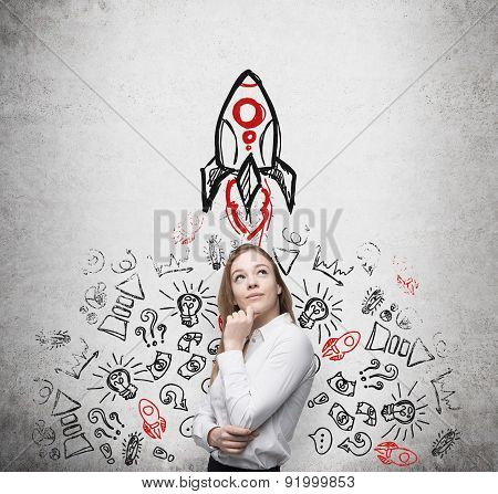 Young Beautiful Business Lady Is Thinking About New Business Ideas. Business Icons And A Rocket Are