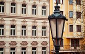 closeup photo of a streetlamp with traditionally Czech facades in the background poster