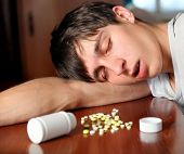Young Man sleep near the Pills on the Table at the Home poster