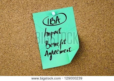 Business Acronym IBA Impact Benefit Agreement written on green paper note pinned on cork board with white thumbtack copy space available poster