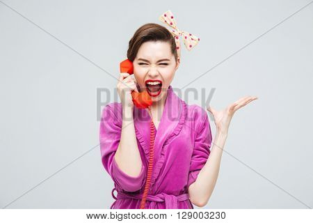 Hysterical young housewife using and screaming in telephone receiver