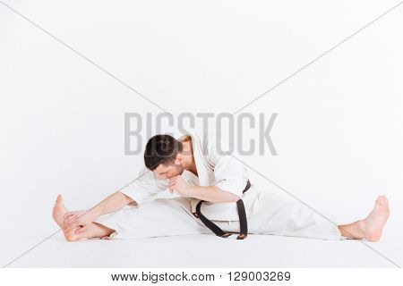 Man in kimono limbering up isolated on a white background