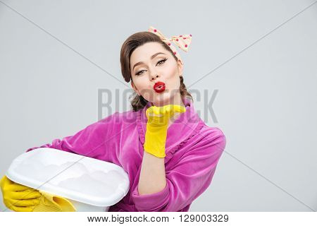 Cute attractive young housewife in protective gloves holding basin with foamed cleanser and sending a kiss