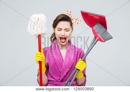 Exhausted hysterical young housewife with mop, cleaning brush and dustpan shouting and crying
