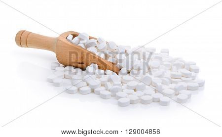 White pills in the scoop on white background
