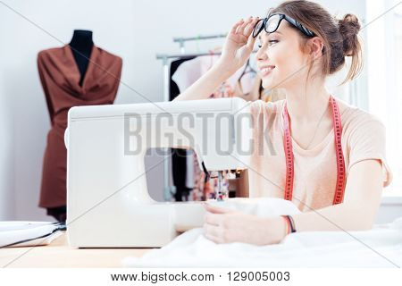 Happy attractive young woman seamstress sitting and sews on sewing machine in studio
