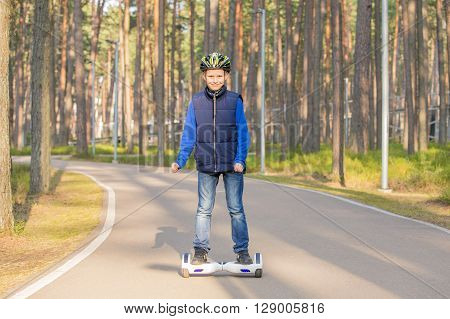 Little boy using electrical scooter in the park