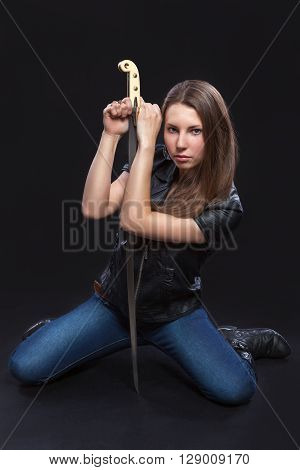 Beautiful brown-haired woman a militant in the leather jacket is sitting on her knees and leans on her sword. Black background.