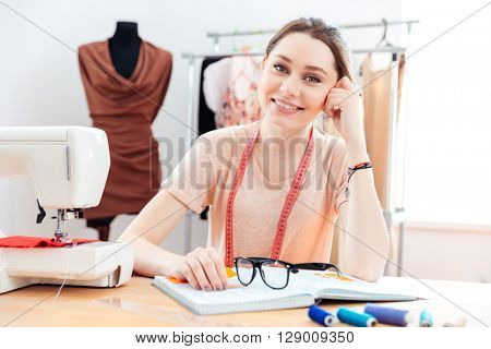 Portrait of cheerful beautiful young woman seamstress working in sewing workshop