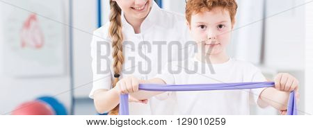 Little boy doing an exercise with the help of pediatric physiotherapist