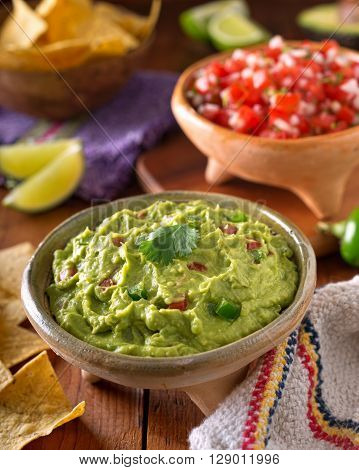 A delicious authentic mexican guacamole dip with avacado lime tomato cilantro and jalapeno pepper.