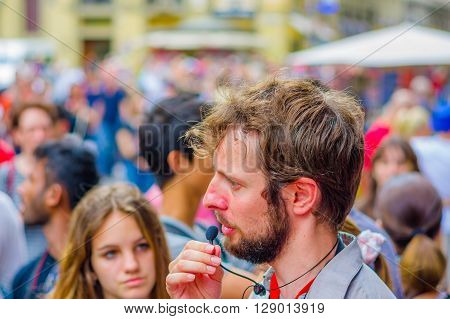 FLORENCE, ITALY - JUNE 12, 2015: Italian tour guide, microphone speaking for a big group of turists. Girl behind paying attention.