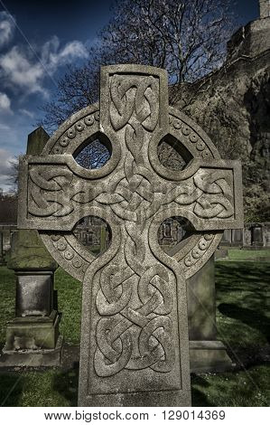Graveyard cross with elaborate Celtic pattern in old cemetery